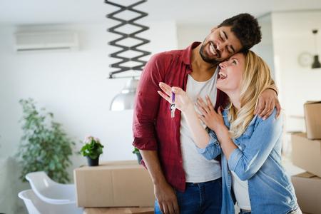 Foto de Young couple unpacking cardboard boxes at new home moving in concept - Imagen libre de derechos