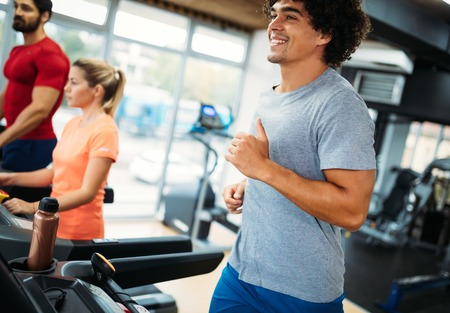 Photo pour Young handsome man doing cardio training in gym - image libre de droit