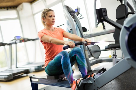 Photo pour Young blonde woman working on rowing machine - image libre de droit