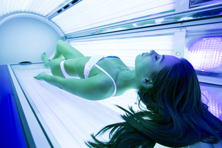 Photo pour Beautiful brunette sunbathing in solarium - image libre de droit