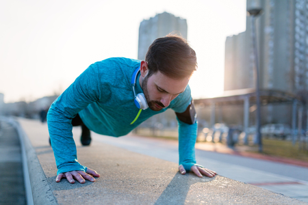 Photo pour Young handsome man doing push ups outdoors - image libre de droit