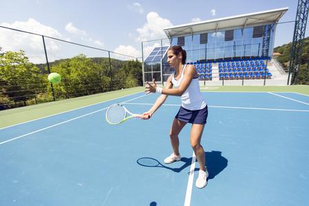 Photo pour Beautiful female tennis player in action - image libre de droit