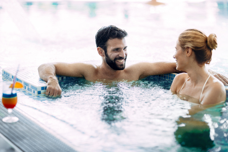 Photo pour Happy attractive couple relaxing in swimming pool - image libre de droit