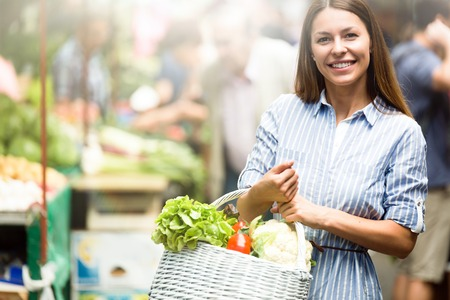Photo pour Picture of woman at marketplace buying vegetables - image libre de droit