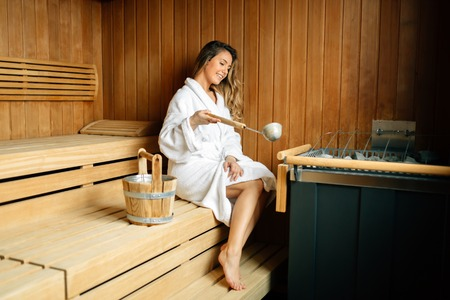 Foto de Beautiful woman sitting in finnish sauna - Imagen libre de derechos
