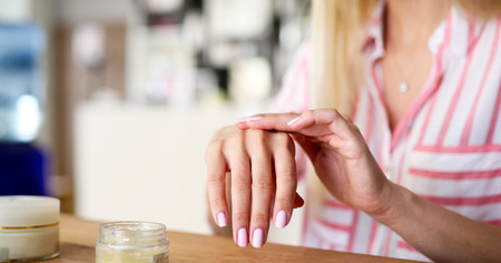 Foto de Woman applying moisturizing cream on hands - Imagen libre de derechos