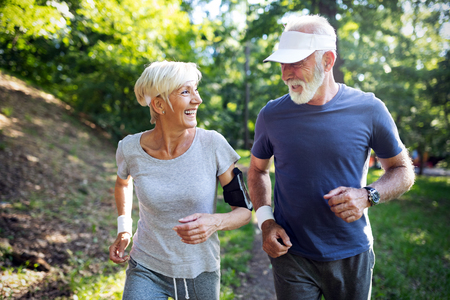 Photo pour Happy fit senior couple exercising in park - image libre de droit