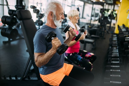 Photo pour Happy senior people doing exercises in gym to stay fit - image libre de droit