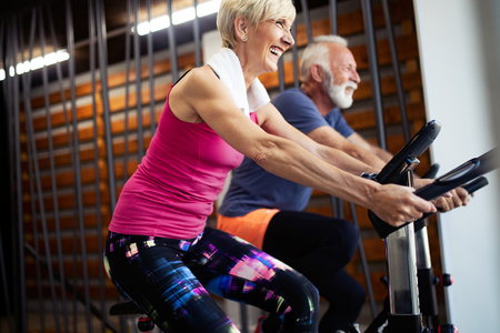 Foto de Mature fit people biking in the gym, exercising legs doing cardio workout cycling bikes - Imagen libre de derechos