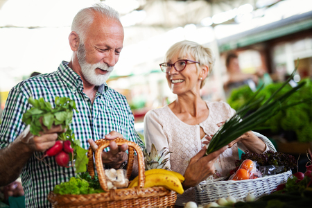 Foto de Shopping, food, sale, consumerism and people concept - happy senior couple buying fresh food - Imagen libre de derechos