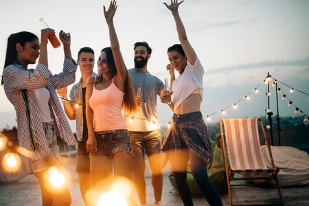 Photo for Carefree group of happy friends enjoying party on rooftop terrace - Royalty Free Image