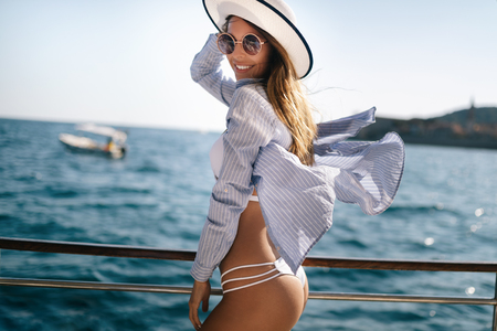 Photo pour Beach vacation. Beautiful woman in sunhat and bikini enjoying summer trip - image libre de droit