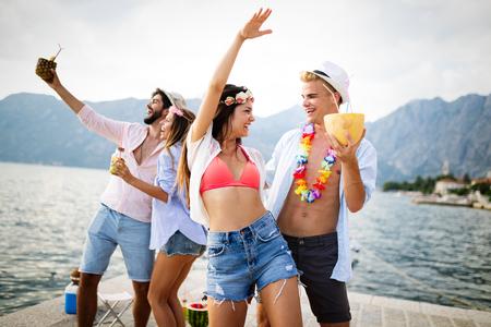 Foto de Group of friends having fun at summer party and drinking cocktail - Imagen libre de derechos