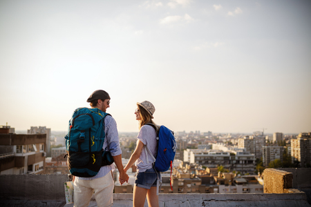 Foto de Multiethnic traveler couple using map together on sunny day - Imagen libre de derechos