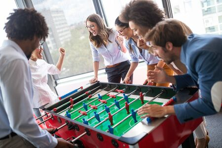 Photo pour Colleagues playing table football in the break. - image libre de droit
