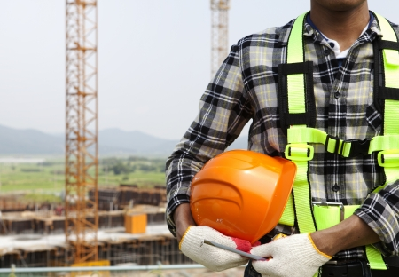 Photo for Close-up construction worker holding helmet, construction safety concept - Royalty Free Image