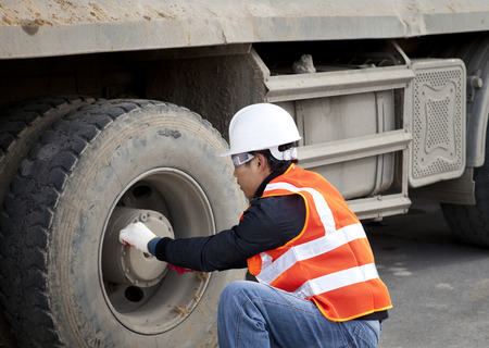 Construction worker checking tyre truck