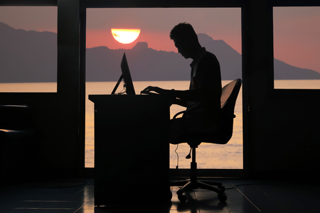 Foto de Silhouette asian business man working on a computer in the evening with sunset background. - Imagen libre de derechos