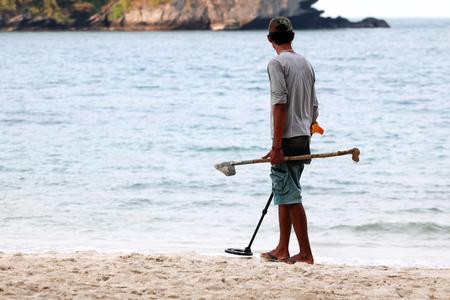 Foto de Asian male uses metal detector to find objects on a beach in Thailand - Imagen libre de derechos