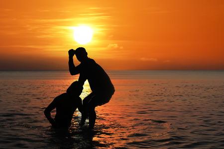 Photo pour Asian man practicing Thai boxing on the sea beach at sunset, Thailand - image libre de droit