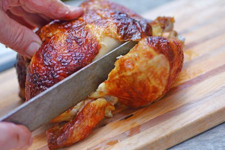 Foto de Closeup of a man slicing into a roast chicken leg - Imagen libre de derechos