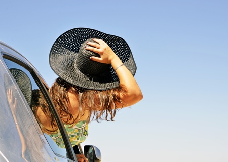 woman holding hat peeking through the car window. Image that represents freedom and happiness during the holidays