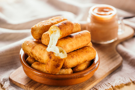 Photo pour Cheese fingers, typical Venezuelan appetizer called tequeños accompanied with a pink sauce on a wooden board - image libre de droit