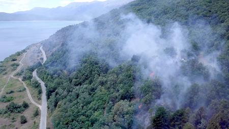 Photo pour smoke of bush fire near village houses in macedonia - image libre de droit