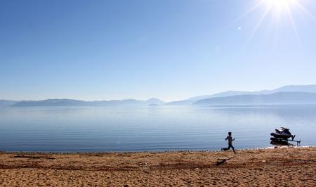 Photo pour unrecognizable boy running on the beach of lake prespa in macedonia - image libre de droit