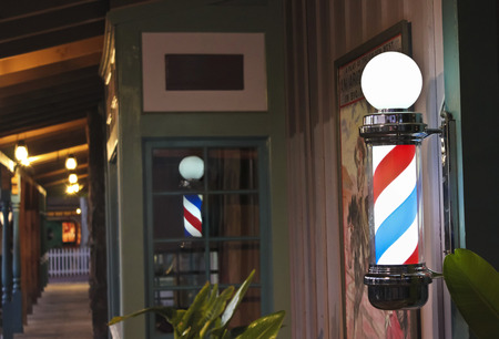 A Glowing Barber Pole on a Barbershop Porch at Night