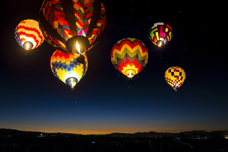 Photo pour Colorful hot air balloons at dawn lit up in the sky. - image libre de droit