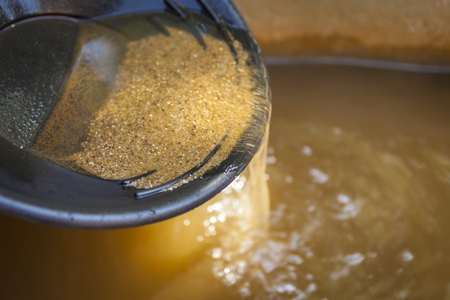 Photo pour Close up of gold panning pan with sifting sand. Shallow depth of field with focus on sand flowing over edge of pan into water. - image libre de droit