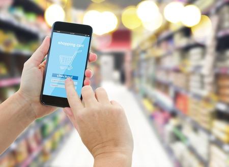 Foto de woman hands holding mobile smart phone with mobile shop  on supermarket blur background  - e-commerce concept - Imagen libre de derechos