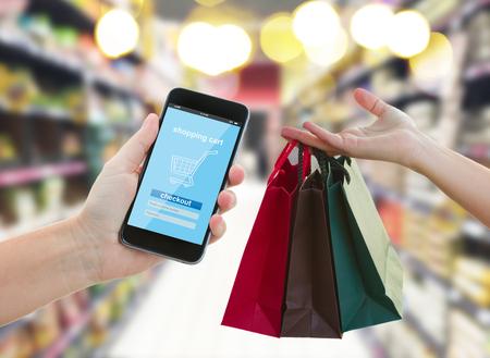 Foto de hand holding mobile smart phone with mobile shop  on supermarket blur background and shopping bags - e-commerce concept - Imagen libre de derechos