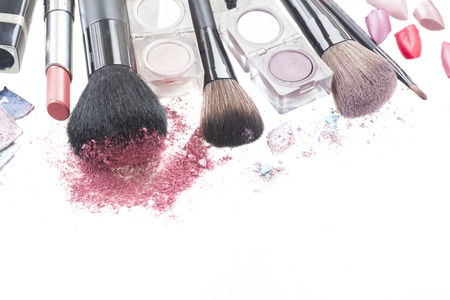 border of  make up brushes, lipsticks and  eye  shadows with crumbles close up  isolated on white background