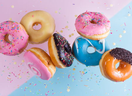 Photo pour flying doughnuts on blue and pink background - image libre de droit
