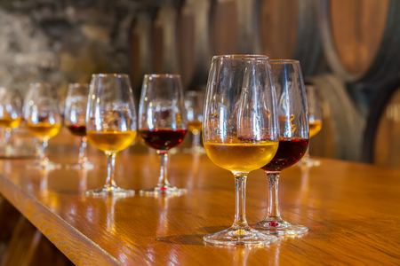 Photo for glasses of red and white port wine with barrels in background, wine degustation - Royalty Free Image