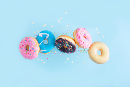 Photo pour flying doughnuts - mix of multicolored sweet donuts with sprinkles on blue background - image libre de droit