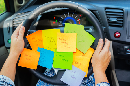 Photo pour Two hands holding driving wheel and to do list in a car - busy day concept - image libre de droit