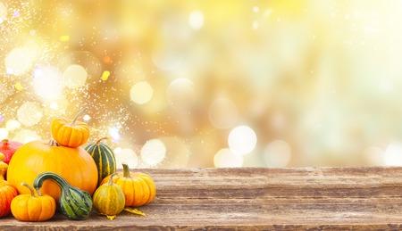 Foto de pile of orange harvest pumpkins with fall leaves on wooden table over fall background banner - Imagen libre de derechos