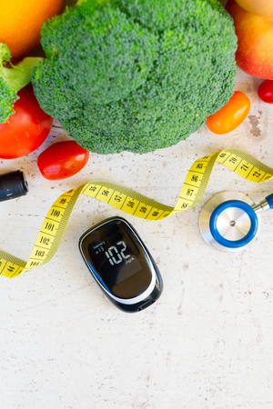Foto per raw vegetables with blood glucose meter, diabetes healthy diet concept - Immagine Royalty Free