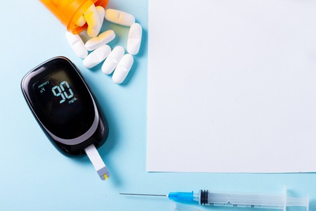 Foto per White pills in orange bottle with blood glucose meter on blue background, copy space on white paper note - Immagine Royalty Free