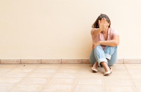 Foto de stressful depressed emotional person with anxiety disorder mental health illness sitting feeling bad with back against wall on the floor and showing a reject gesture - Imagen libre de derechos