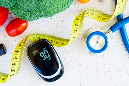 Foto per raw vegetables with blood glucose meter and stethoscope, close up, diabetes healthy diet concept - Immagine Royalty Free
