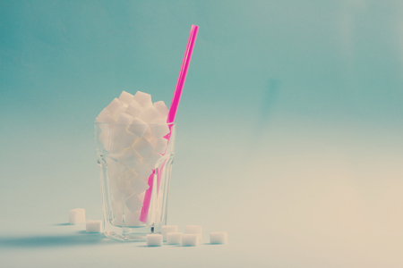 Foto per Sugar white cubes in glass, diabetes and sugar overuse concept, blue background with copy space, retro toned - Immagine Royalty Free