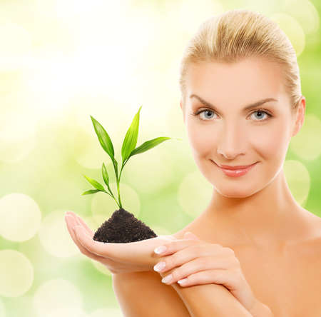 Beautiful blond woman with young plant over abstract blurred background
