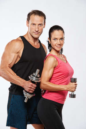 Photo pour Athletic man and woman with a dumbells. - image libre de droit