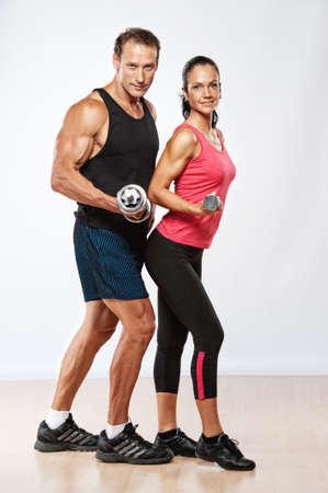 Photo pour Athletic man and woman with a dumbells. - image libre de droit