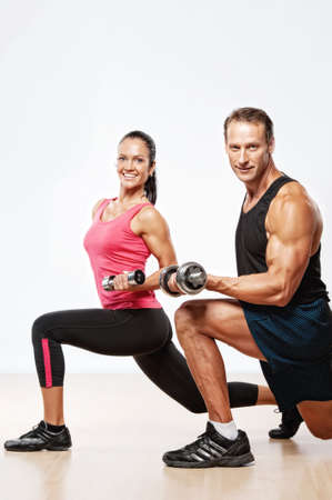 Photo for Athletic man and woman with a dumbells. - Royalty Free Image