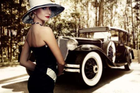 Photo pour Woman in hat against retro car. - image libre de droit